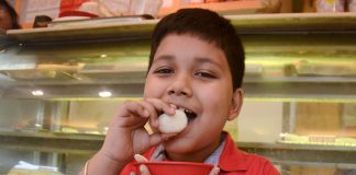 A boy eating rasogolla at a sweets shop in Kolkata on Tuesday