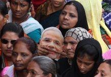 Women holding Modi masks