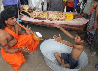 A boy prays to a man dressed as Narada to invoke rains.