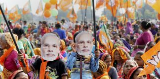 People wearing masks of Modi at a rally