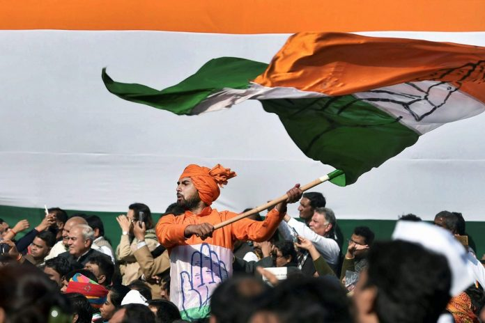 A Congress party spokesperson waves the party flag during a ceremony