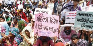 women sitting in protest with written slogans to stop crime against Dalit women