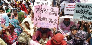 Women sitting in protest with written slogans to stop crime against