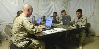 U.S. marines using computers in a tent