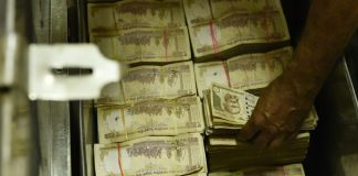 An employee stacks old currency notes at an exchange counter at Allahabad Bank, branch of Parliament Street on November 10, 2016 in New Delhi, India.