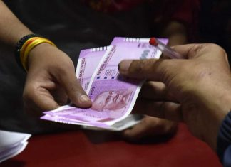 A Rs 2000 note being handed over in a bank