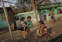 A villager sits with his family in the village of Guhanwadi near Jharia in Jharkhand