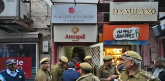 Police personnel outside shops in the Khan Market, in New Delhi on Monday.