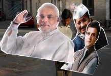 An Indian worker holds cut-outs Narendra Modi, Rahul Gandhi, and Arvind Kejriwal