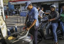 A worker refuels a scooter | Dhiraj Singh/Bloomberg