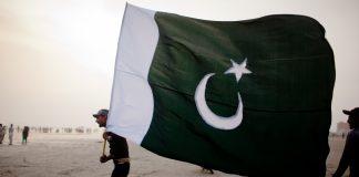 A man walks with a Pakistan National flag | Daniel Berehulak/Getty Images